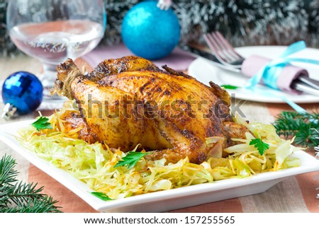 Roasted whole chicken with golden crust and garnish of stewed cabbage, festive Christmas dinner - stock photo