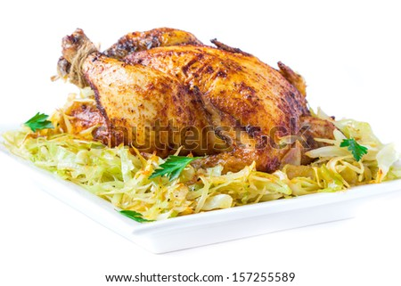 Roasted whole chicken with golden crust and garnish of stewed cabbage, isolated on white background - stock photo