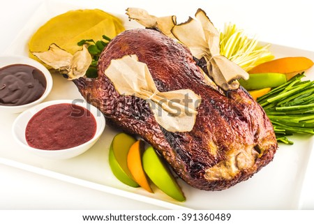 Roasted whole chicken with sauces, fruits and herbs on a plate