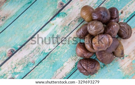 Roasted whole peeled chestnut over wooden background - stock photo