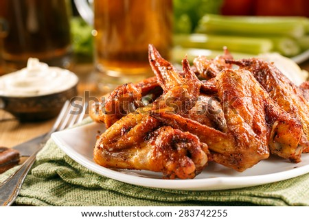 Roasted wings on the plate with sauce and beer on background, close-up. Selective focus, dramatic shooting angle. - stock photo