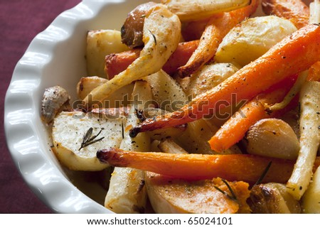 Roasted winter vegetables, in serving bowl.  Including carrots, parsnip, potato, butternut squash, garlic bulbs, and eschallots. Garnished with rosemary.