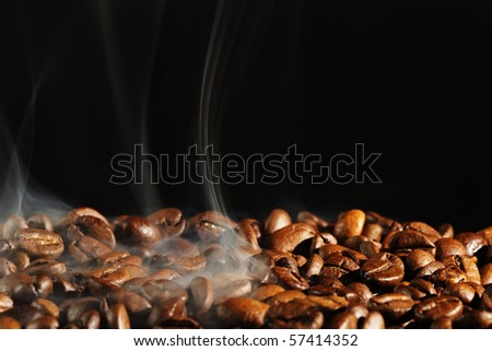 roasting coffe with smoke and black background - stock photo