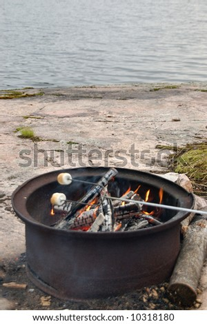 Roasting marshmallows in the great outdoors.  Canada. - stock photo