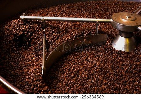 Roasting process of coffee. Coffee beans moved by the rotating shovel inside the hopper for cooling down and screening after roasting. Drum type roaster - stock photo