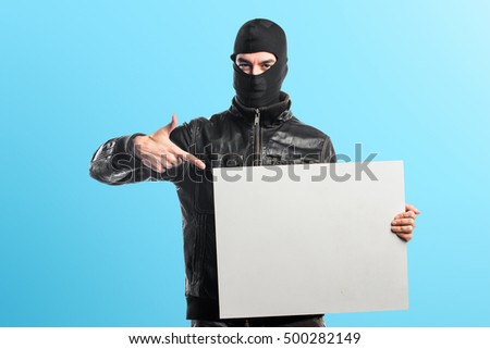 Robber holding an empty placard over colorful backgound