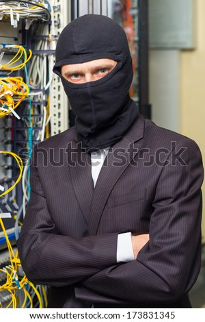 robber in black mask in the server room hack, and steals information, unauthorized downloading data - stock photo