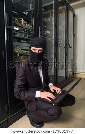 robber in black mask in the server room hack, and steals information, unauthorized downloading data on a laptop - stock photo