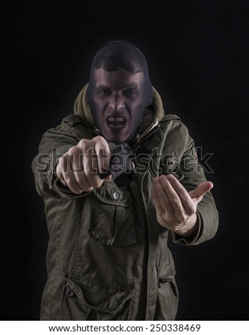 Robber pointing gun at camera - stock photo