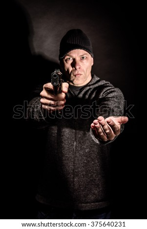 Robber with a gun holds his hand out for the money, concept of danger, threat and extortion - stock photo