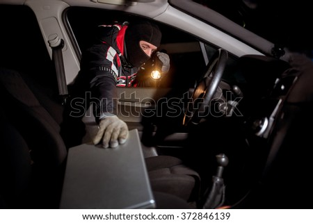 robber with a mask on his face holds the battery and looks what will steal the car,night time - stock photo