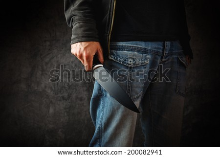 Robber with big knife - a killer person with sharp knife about to commit a homicide, murder scenery. - stock photo