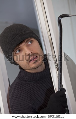 robber with crowbar breaking into a house - stock photo