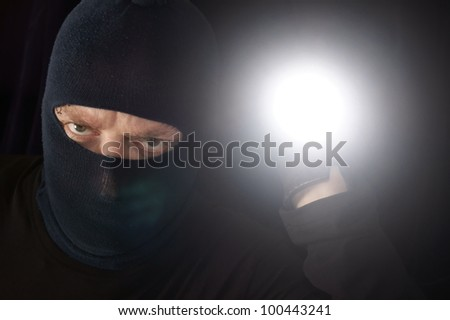 Robber with torch - stock photo