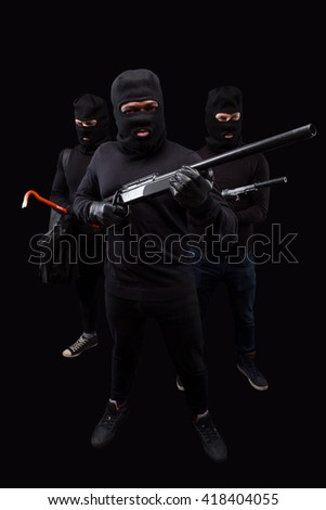 Robbers posing with rifles and crowbars in full length in studio. Robbery, burglary and mafia concepts over black background.  Isolated on black. - stock photo