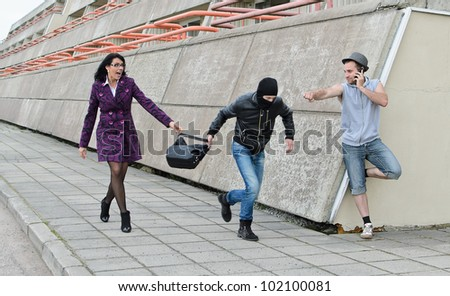 Robbery prevention on the street. Thief try to steal a bag. - stock photo