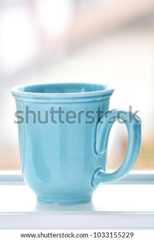 Robinâ??s egg blue mug in vertical format.  Blurred background with room for text.