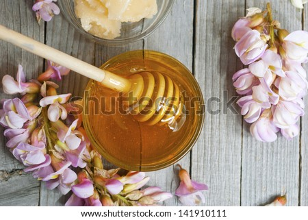robinia honey with acacia blossoms on wooden table - stock photo
