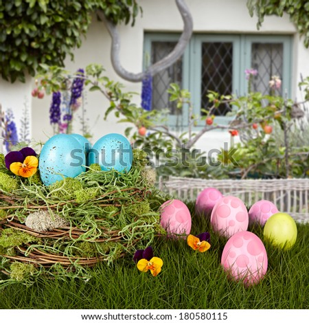 Robins Blue Easter Eggs In Bird Nest, Green Grass With Pink & Purple Holiday Decorations & Flower Garden Cottage Background - stock photo