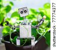 Robot among green leaves holding a turned-on lightbulb in his hand - stock photo