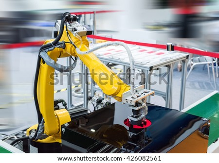 Robot arm in a factory working - stock photo