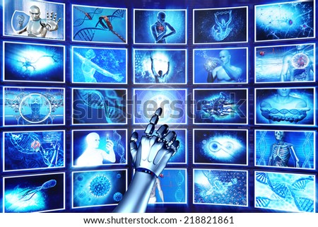 Robot arm pointing at hi-tech screens - stock photo