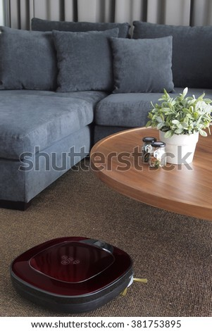 Robot vacuum cleaner cleaning the floor in cozy living room. - stock photo