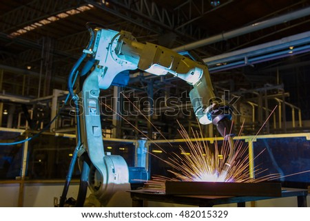 Robot welding metal in assembly line