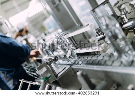 Robotic factory line for processing and bottling of pure spring water into canisters and bottles. Selective focus. Short depth of field.