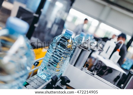 Robotic factory line for processing and quality control of pure spring water bottled into canisters. Short depth of field and selective focus. Unrecognizable people in background.