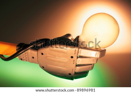 Robotic Hand Holding Lightbulb with Warm and Green Glows - stock photo