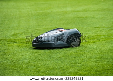 Robotic lawn mower on grass, side view - stock photo