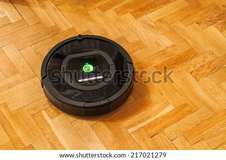 Robotic vacuum cleaner on parquet - technology housework - stock photo