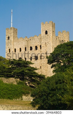 Rochester castle with green trees against a clear blue sky - stock photo