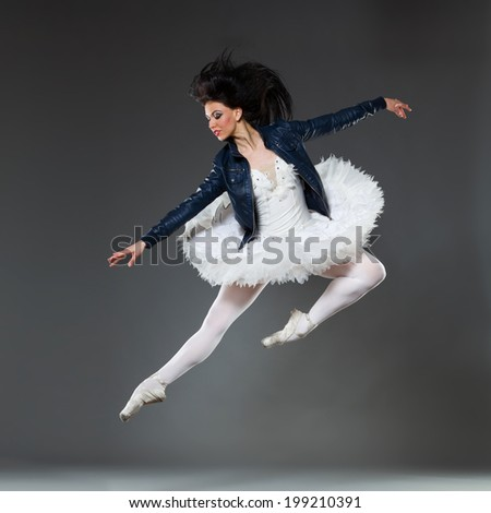 Rock and ballet. Jumping ballet dancer wearing leather jacket. Full length studio shot on gray background.