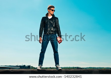 Rock and roll man 50s style with black jacket. Holding portable radio. On rooftop. Blue sky. - stock photo