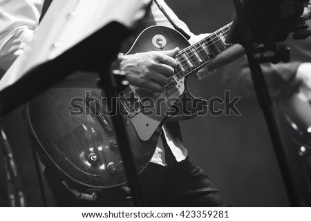Rock and roll music background, guitar players on a stage, black and white, selective focus - stock photo