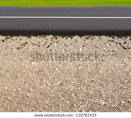 Rock and soil material on the new paved road in the rural areas. - stock photo