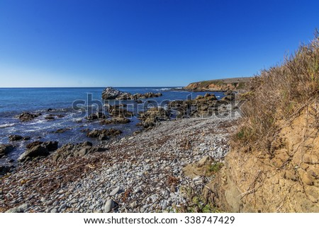 Rock and unusual geological formations at low tide, waves crashing on a rocky beach making sea foam on Moonstone Beach, along the rugged Big Sur, coastline, California Central Coast, near Cambria CA. - stock photo