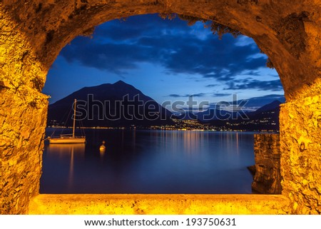 Rock arch opening overlooking lake Como in Italy on a tranquil evening. Lights from Menaggio village twinkling at the base of the mountains in the distance. - stock photo
