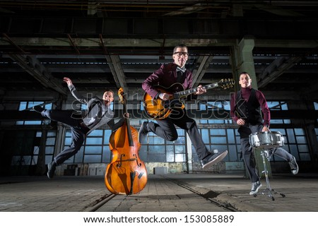 Rock band jumps into the air in an old industrial building - stock photo