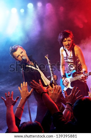 Rock band live on stage performing for his fans - stock photo