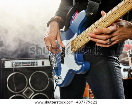Rock band performs on stage. Bassist in the foreground. Close-up. - stock photo