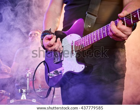 Rock band performs on stage. Guitarist, bass guitar and drums. Guitarist in the foreground. Close-up. - stock photo