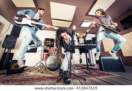 Rock band playing hard rock in the studio. Concept about entertainment and music - stock photo