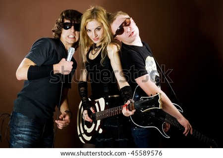 Rock band playing in studio on brown background - stock photo