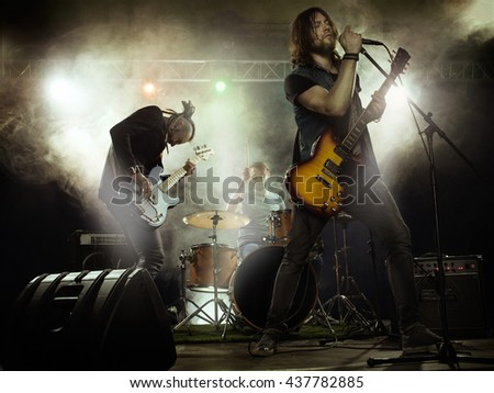 Rock band playing on stage. Solo guitar, bass and drums. - stock photo
