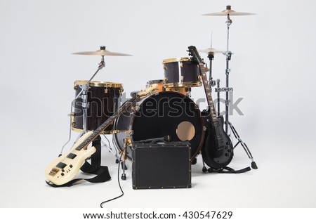 Rock Band, solo guitar, bass, drums, microphone on a black suitcase. - stock photo
