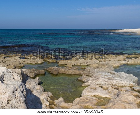 rock beach with small ponds Turquoise water and blue sky