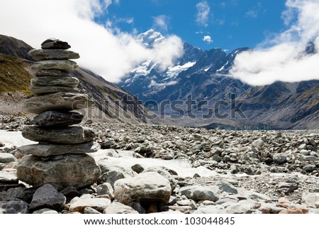 Rock cairn in Hooker Valley on a trail leading to Aoraki, Mount Cook, highest peak of Southern Alps, an icon of New Zealand partially covered in clouds - stock photo